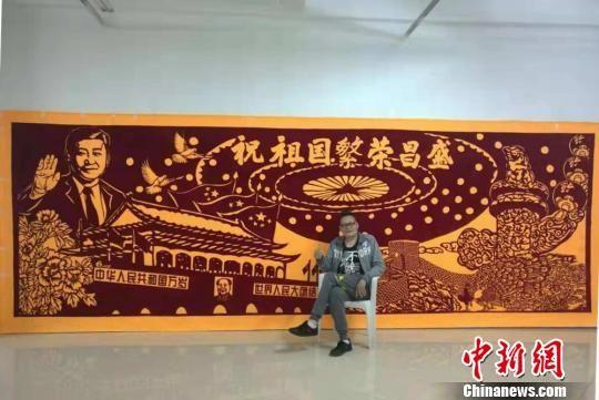 邢浩南对他刚刚创作完成的巨幅剪布作品《祝祖国繁荣昌盛》非常满意。 朱志庚 摄
