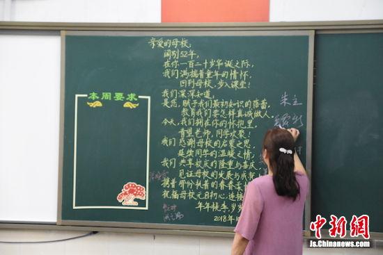 阔别母校52年,如今再来黑板前写下祝福。