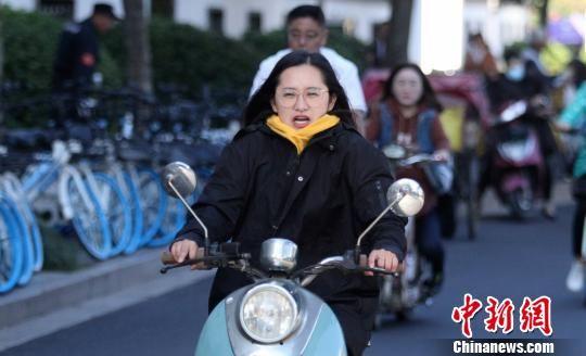 图为10月10日,受冷空气影响,出行的市民纷纷换上了秋装。 崔佳明 摄