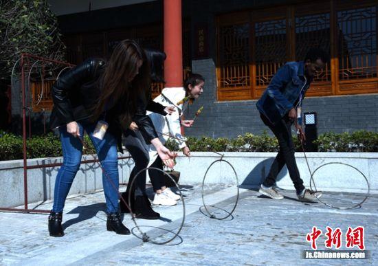 外国友人即兴玩起推铁环大赛。
