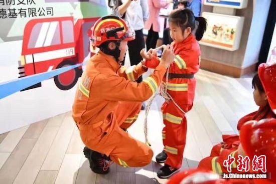 消防队员对萌娃们互动。