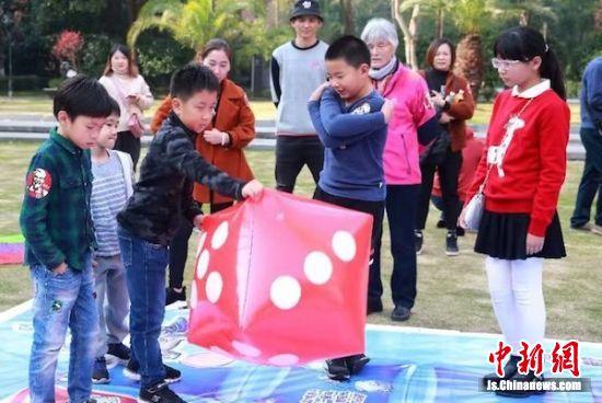小朋友们参与真人棋盘游戏。