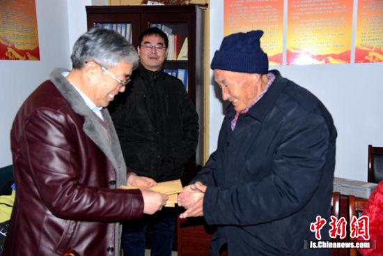 原丰县欢口镇党委书记杨金海向学生家人发放助学金。