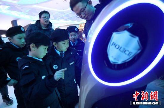 江苏少年警校的小学警被亮相的警务机器人吸引。中新社记者 泱波 摄