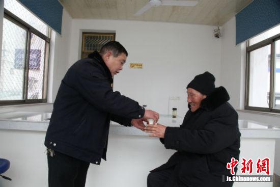 协警王瑞伟给老人倒茶。