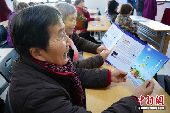 市民们阅读防欺诈科普宣传手册。