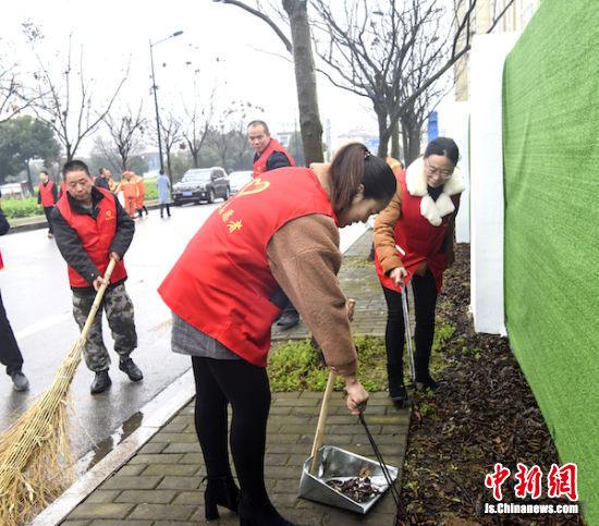 图为志愿服务团成员在清理墙体周边杂草。