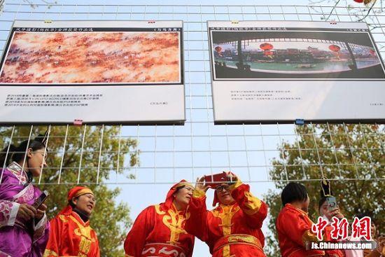 参与民俗表演的村民观看摄影作品。中新社记者 泱波 摄