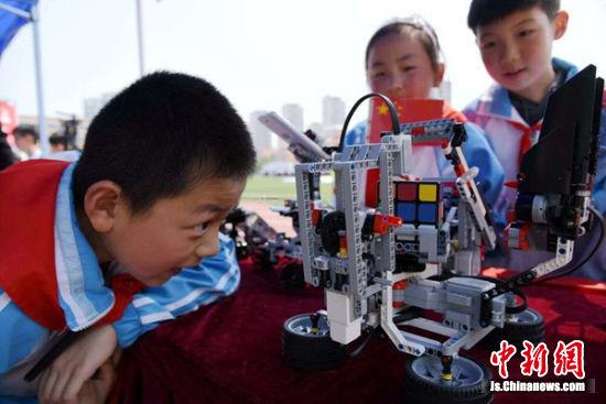 小学生们对机器人产生浓厚兴趣。朱志庚摄