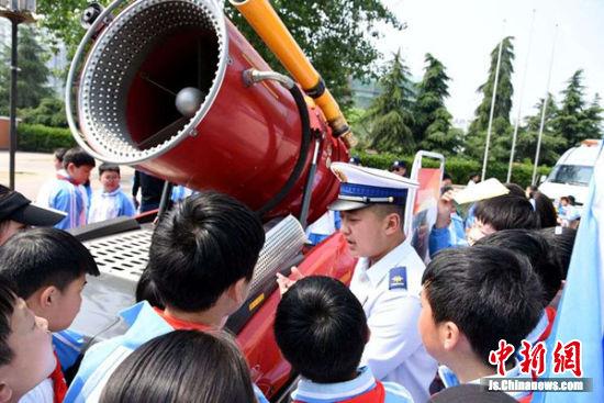 消防队员为学生们解说灭火机器人的奥秘。朱志庚摄