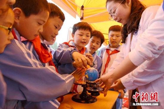 众多孩子们亲手操作三球仪,探索太阳地球月球的关系。朱志庚摄