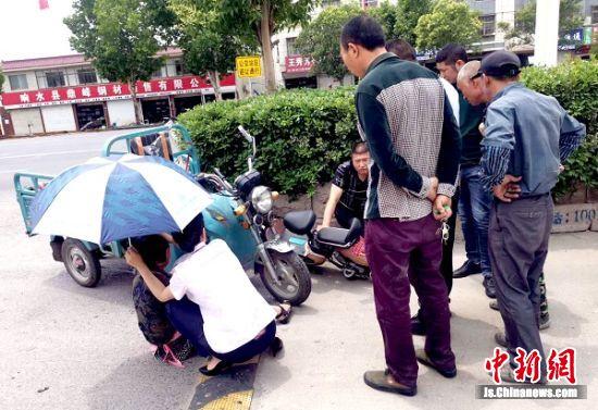 老人遭車禍受傷倒地 供電公司員工為老人撐傘遮陽