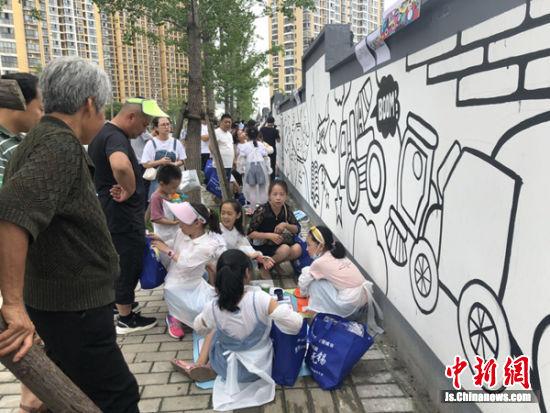 墙绘活动引来了很多围观群众。