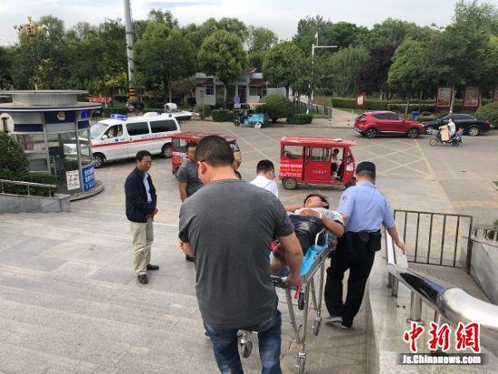 民警和医生将醉酒男子送上救护车