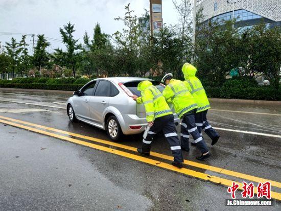 沛县交警帮助推出遇到深水熄火的轿车。