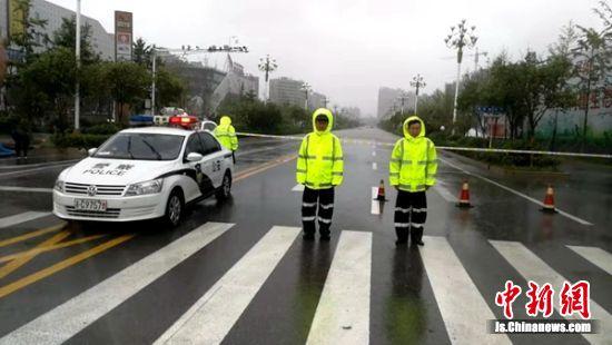 低洼路段严重积水,为防车辆遇险,沛县交警冒雨守候路口警戒线外。