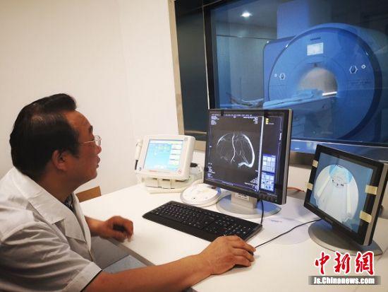 海门人民医院的医生正在调试新设备,新设备能把大脑里的静脉看得清清楚楚。 陆建国 摄