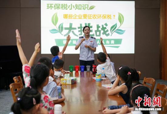 图为工作人员为小朋友们普及环保知识。