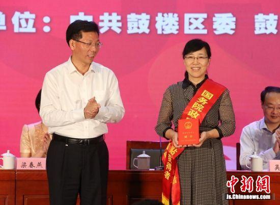 南京市鼓楼区区委书记刘军向国务院政府特殊津贴获得者、鼓楼幼儿园园长颁发证书。徐琦摄。