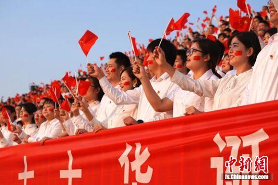 老师们挥舞国旗,动情演唱《我和我的祖国》。