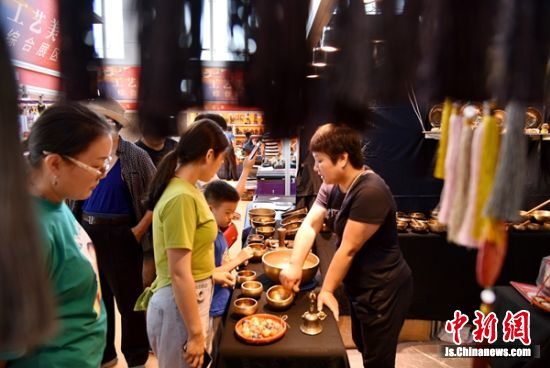 铜器生钵展位引来众多体验者。