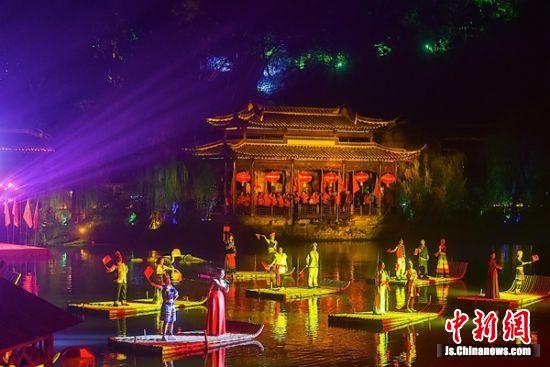 身着鲜艳民族服饰的演员们在玉泉湖的竹筏上深情唱响山歌。钟学满摄