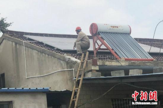 电力工人在严开权家屋顶检查光伏电板。