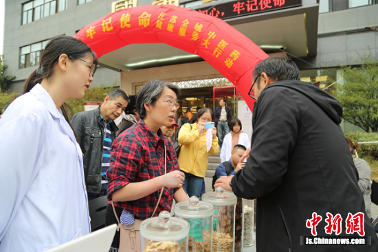 位于南京中医药大学汉中门校区国医堂的服务点,南京中医药大学药学院专家向市民讲解中药知识