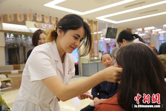 南京中医药大学留学生为市民提供中医耳穴埋籽体验。
