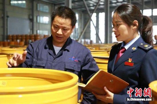 图为税务干部在华鼎车轮生产一线了解研发工艺。
