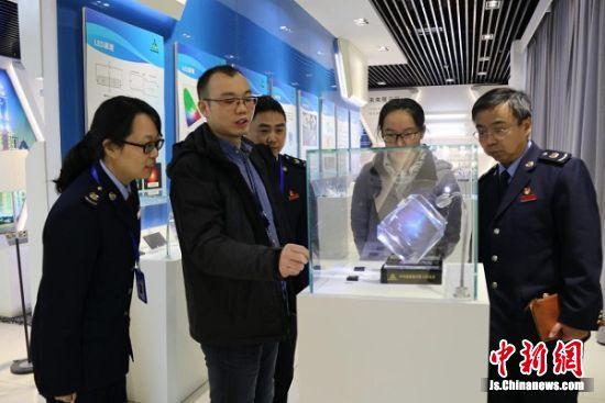 图为华灿光电工作人员向税务干部介绍芯片产品。