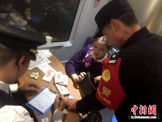 乘警会同列车工作人员清点包内财物。