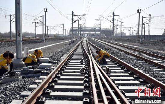工人们在淮安东站北咽喉高速道岔整体调试。 朱志庚 摄