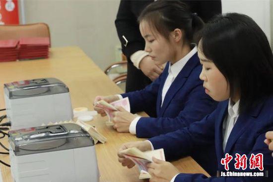 """学生们在展示""""花式点钞""""技艺。"""