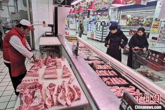 资料图:超市工作人员分解猪肉。 中新社记者 张云 摄