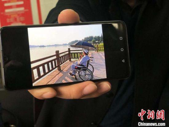 王亚展示父亲病重后眺望矿山社区照片。 刘林 摄