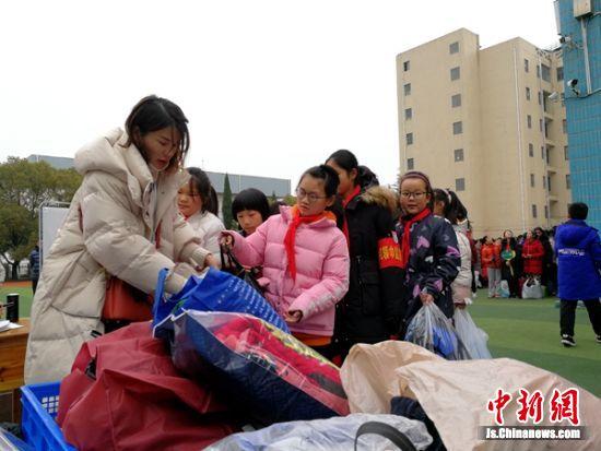 """同学们排起长队一起来捐赠衣物""""送温暖""""。"""