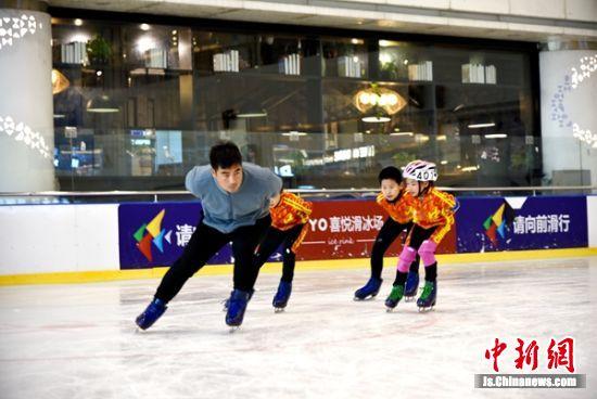 教练现场认真传授冰上技巧。