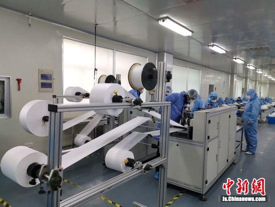 1月28日,在位于江苏淀山湖镇的昆山洁宏无纺布制品有限公司,一次性医用护理口罩制造设备正全速运转,工人们正埋头赶制。