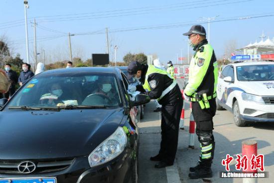 在滨海县大套卡口,现场工作人员正在对过往车辆进行登记检查。