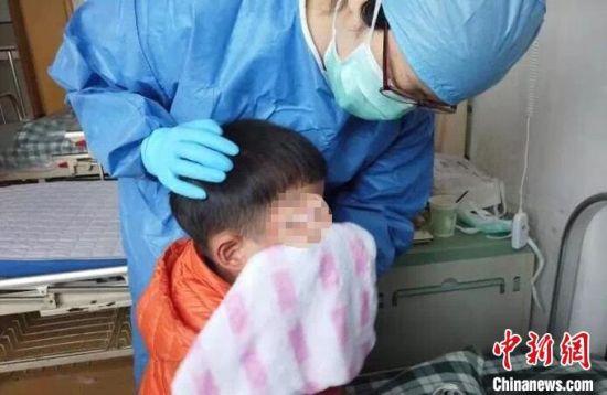"""5岁男童妈妈确诊后,护士组成了""""妈妈团""""充当起""""临时妈妈""""。图为护士照料园园(化名)。 """"临时妈妈微信群""""中截图 摄"""
