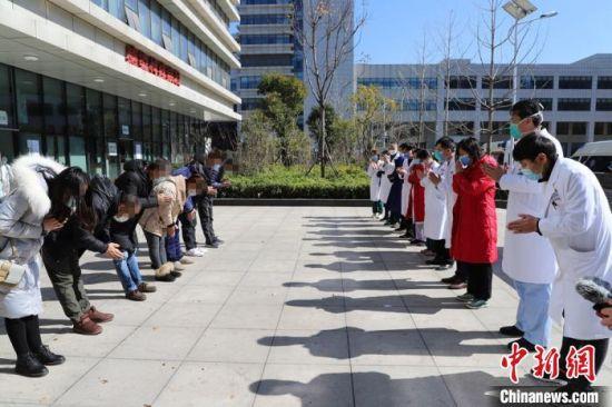 康复出院患者集体向医护人员鞠躬致敬。 王以坤 摄