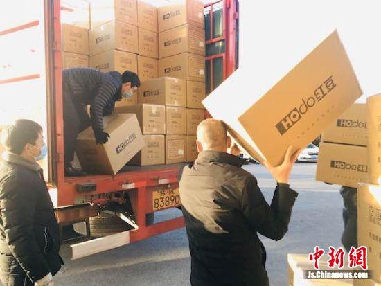 4万件一次性医用隔离衣搬上卡车。