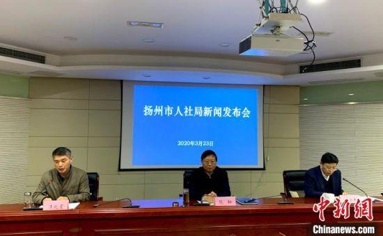 扬州市社会保险基金管理中心主任汪兆星(左一)通报该市社会保险费减免政策。 崔佳明 摄