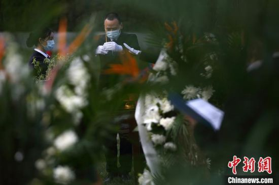 身穿黑色衣装的陵园祭拜工作人员将手中素果、美酒、清香向上举起,果果实心、杯杯清酒、炷炷清香送逝去亲人。 泱波 摄