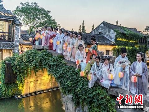 年轻人身着古服夜游江南古镇周庄,感受夜色绮丽的别样水乡。