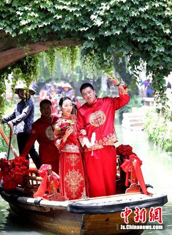 """""""520""""百人婚典在水乡周庄举行,新人们体验水上接亲。"""
