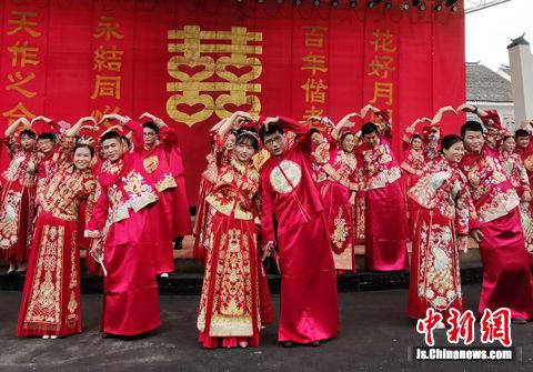 """""""520""""百人婚典在水乡周庄举行,新人们在集体婚礼仪式上""""比心""""示爱。"""