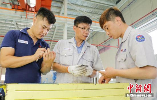 大韩汽车配件有限公司生产次长崔璇途(中)指导员工革新生产工艺 郜野乔。
