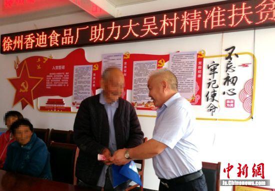 爱心企业主闫龙现场为村民发放防暑降温费。